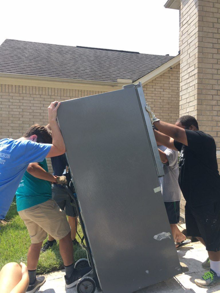 Orchestra members help family move damaged furniture and appliances.