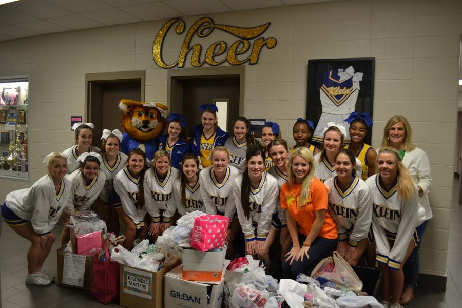 The cheerleaders gather around the collection of items donated by students, organizations and faculty throughout the Kindness Matters campaign. Running from mid-November to Dec. 5, the cheerleaders donated the items on Dec. 9. Photo by Sierra Schuman.