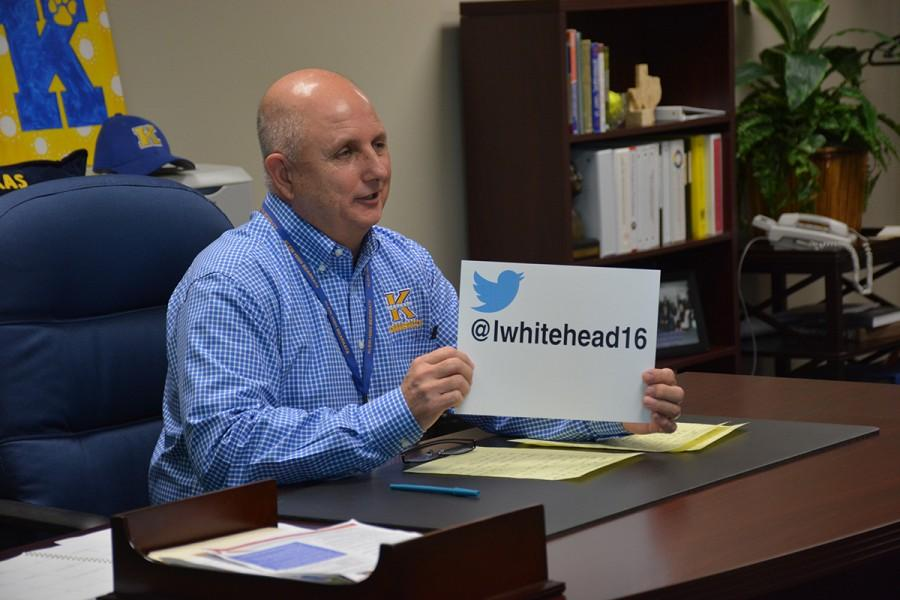 Mr.Whitehead holding a sign that says his twitter account name