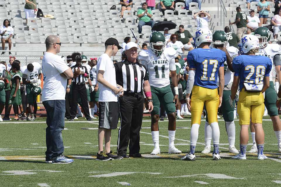 Jacob and his dad participate in the coin toss.