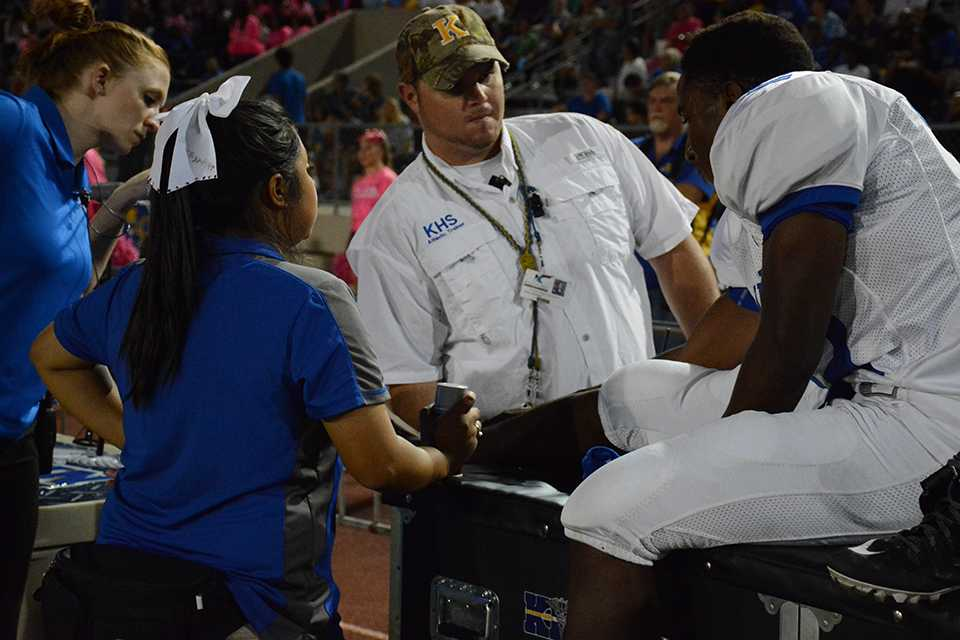 Trainers assist football player during game. Concussions are a large concern for football players.
