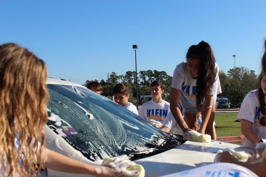 Members of several sports teams help wash cars during Klein Serves.