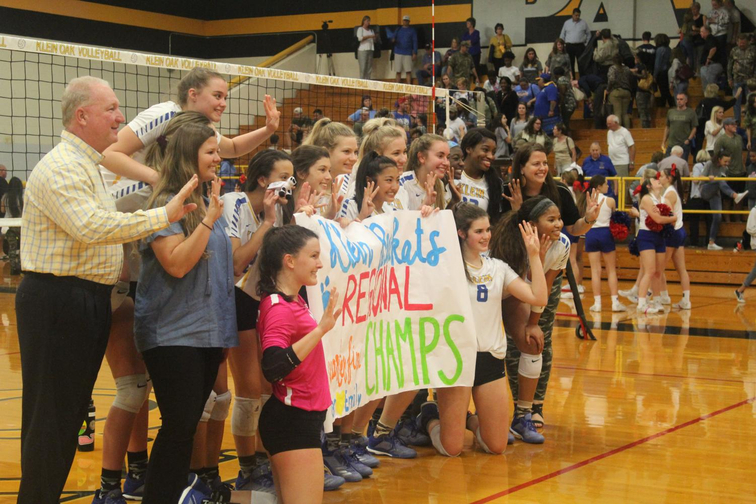 The lady Kats hold a sign to celebrate their round 3 playoff victory.