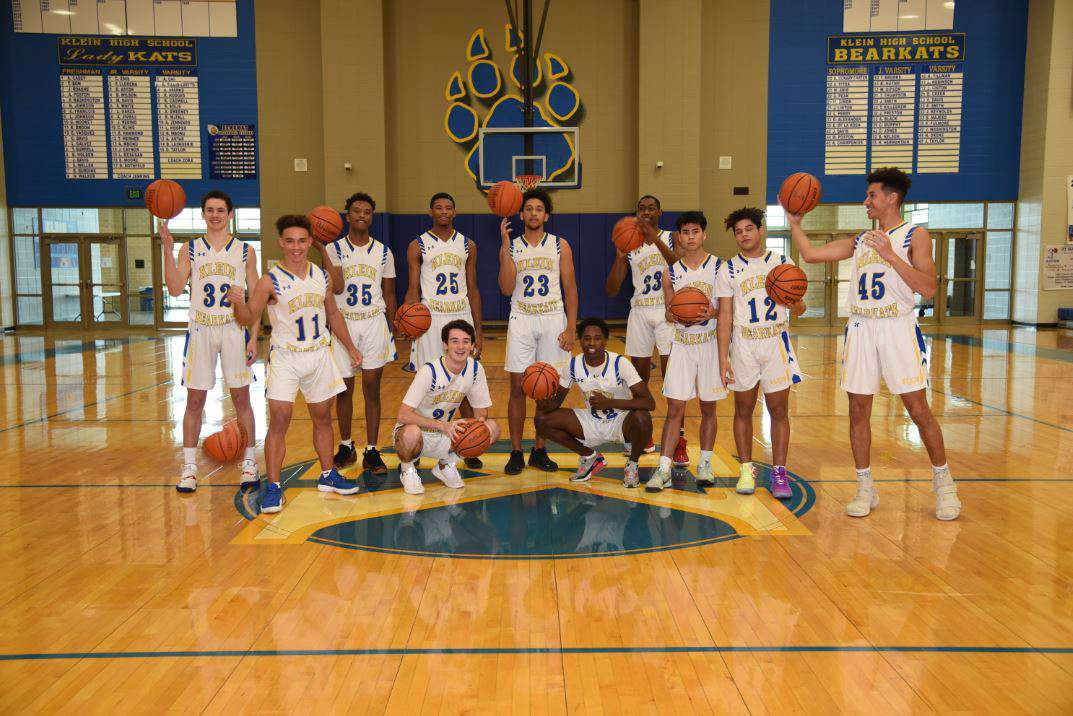 Varsity team pose with basketballs.