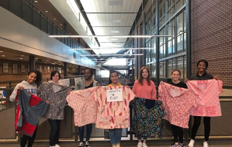 Fashion design students stand next to each other holding the smocks they created.
