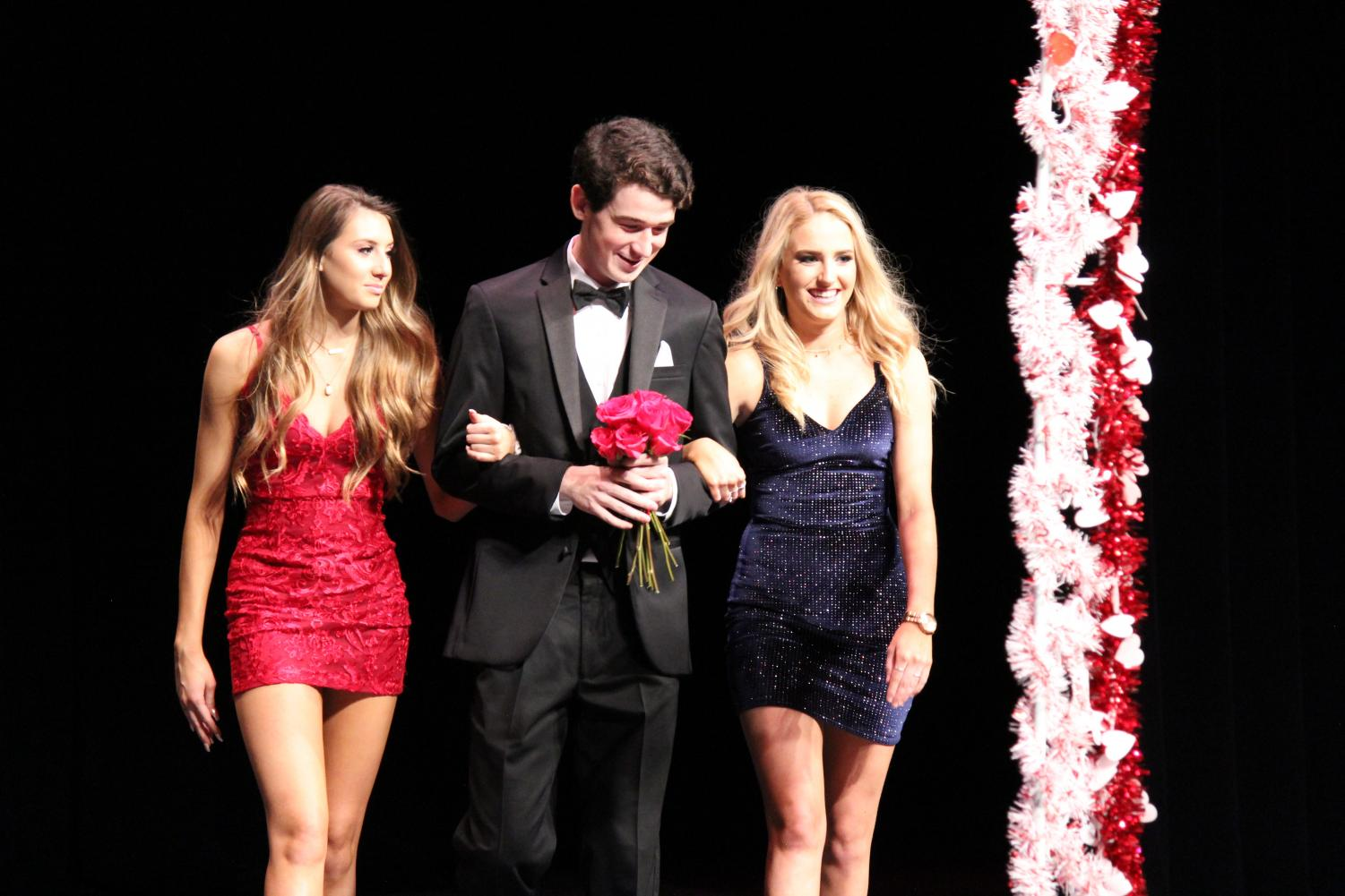 Senior+Jack+Smith+walks+with+his+escorts+as+he+holds+flowers.