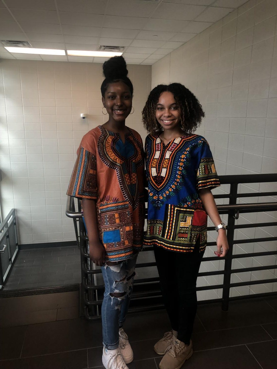Seniors Myah McNair and Maya Monroe dressed in African patterened shirts.